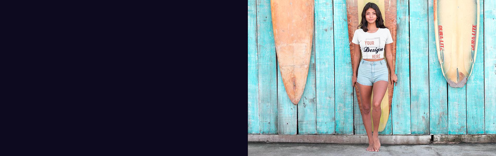 Junge Frau steht vor Surfboards und träg T-Shirt von T-Shirt bedrucken Deutschland